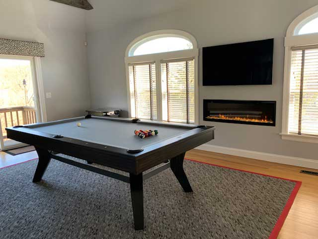pool table on a grey and red rug with a wall fireplace
